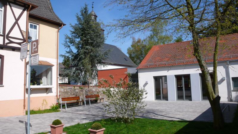 Rechts: Gemeindehaus, links: Pfarrhaus, im Hintergrund: die Kirche